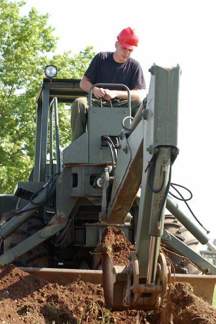 US Air Force (USAF) AIRMAN First Class (A1C) Timothy Sexton, 31st Communications Squadron (CS) operates a backhoe during a cable reconstruction project at Aviano Air Base (AB), Italy