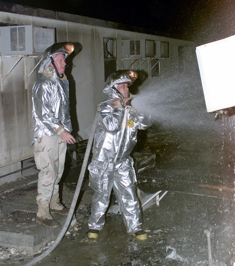 US Air Force (USAF) MASTER Sergeant (MSGT) Robert Wimer (left) stands by as SENIOR AIRMAN (SRA) Jeremy Pata, a Firefighter assigned with the 379th Expeditionary Civil Engineer Squadron (ECES) mans a fire hose while responding to a modular trailer fire at Al Udeid Air Base (AB), Qatar, during Operation ENDURING FREEDOM