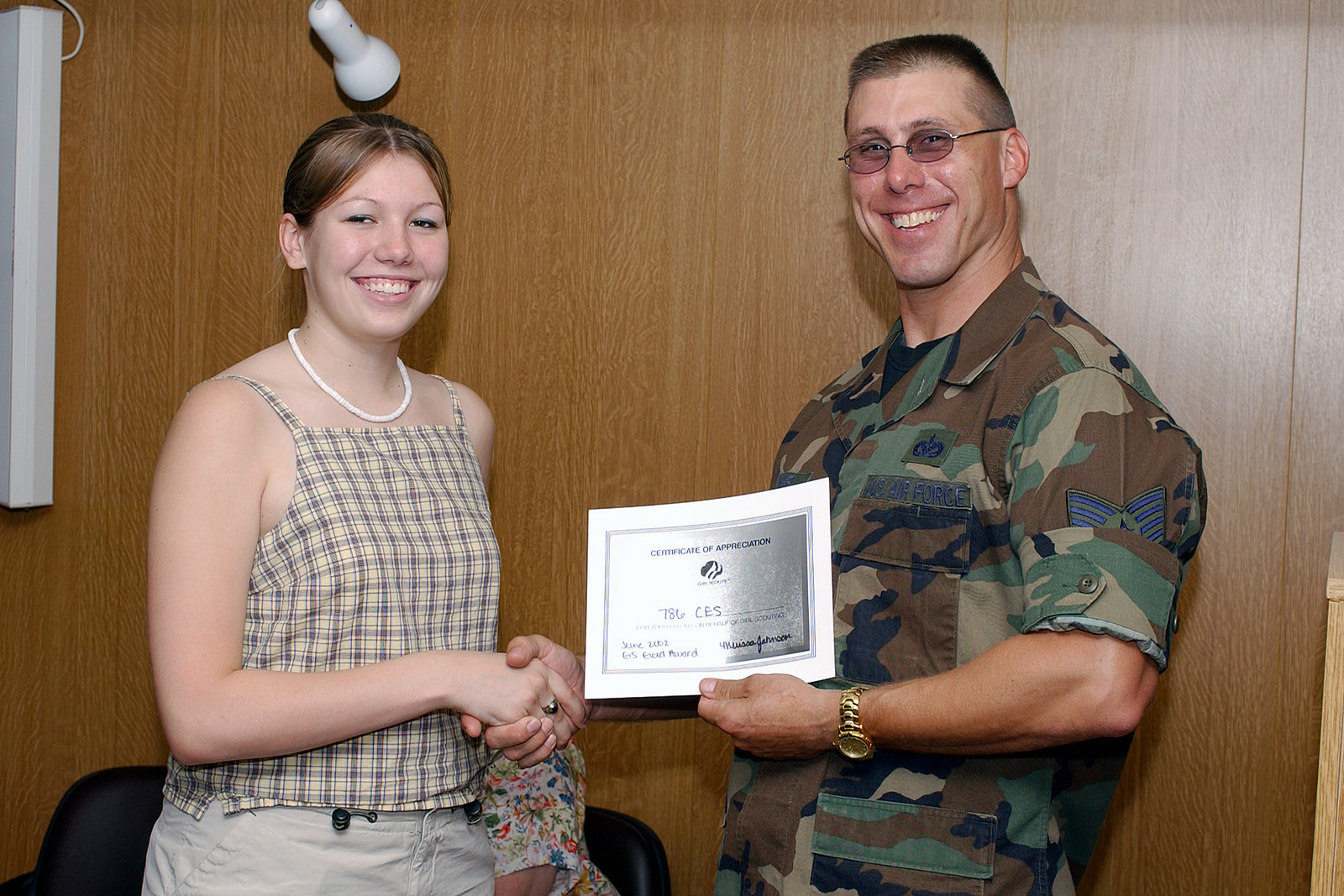 Melissa Johnson (left), a former student atKaiserslautern High School, Germany, presents US Air Force (USAF) Technical Sergeant (TSGT) Michael Kunkel, 786th Civil Engineering Squadron (CES) with a certificate of appreciation for his help with raising school supplies for a Bosnian Schools