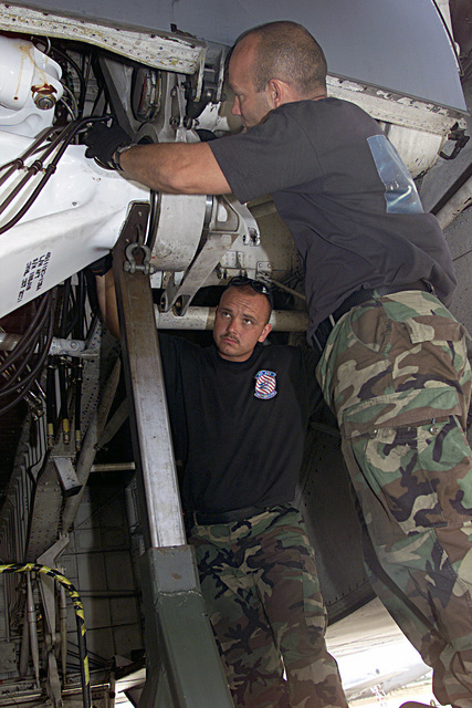 US Air Force (USAF) Technical Sergeant (TSGT) Keith Rouselle (foreground), and USAF STAFF Sergeant (SSGT) Mark Nowak, both Aerospace Repair SPECIALIST assigned to the 439th Aircraft Generation Squadron (AGS), 439th Airlift Wing (AW), Massachusetts (MA) Air National Guard (ANG), work on removing a main landing gear strut from a USAF C-5A Galaxy aircraft while deployed at Moron Air Base (AB), Spain, in support of Operation ENDURING FREEDOM