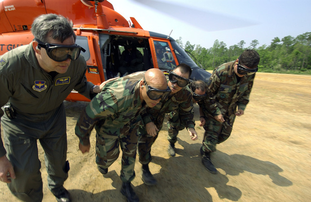 After loading a simulated patient, U.S. Air Force Aerospace Medical personnel from the 916th Aerospace Medical Flight, Seymour Johnson, N.C., prepare to evacuate the area prior to a U.S. Coast Guard HH-65 helicopter taking off during Exercise LIFESAVER, May 24, 2005. (U.S. Air Force photo by TECH SGT. Jerry Morrison) (Released)