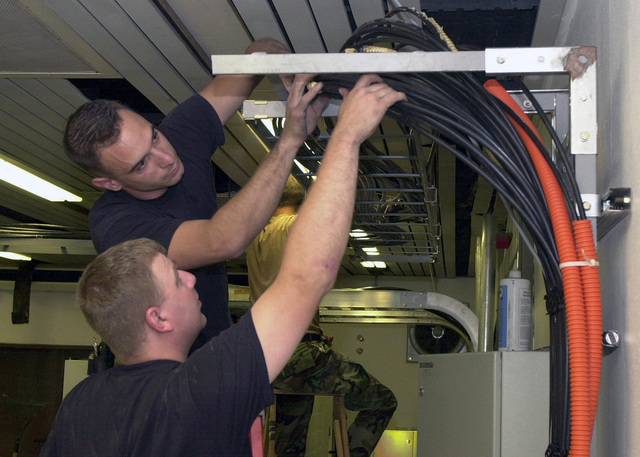 US Air Force (USAF) AIRMAN First Class (A1C) Aaron Ratcliff (foreground) and USAF A1C Matthew Davidson (background), both assigned to the 86th Communications Squadron (CS), assist USAF SENIOR AIRMAN (SRA) Robert Tallon, Detachment 1, Computer Systems Squadron, with installing fiber optics cable inside the US Air Forces in Europe (USAFE) Network Operations Center, at Ramstein Air Base (AB), Germany