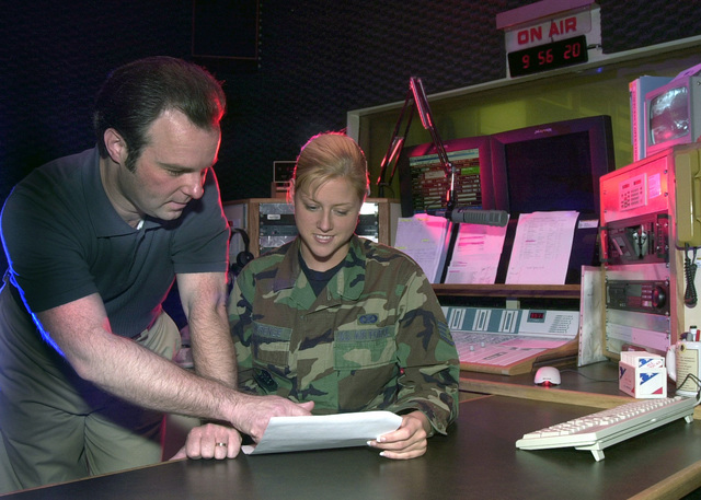 Mr. Jerry Cormier (left), Broadcast Director and US Air Force (USAF) STAFF Sergeant (SSGT) April Lawrence, News Department Non-Commissioned Officer In Charge (NOCIC), both assigned to the Armed Forces Network (AFN), Kaiserslautern, Germany, discuss programming changes to be implemented for the new Z 100.2 radio program. The AFN Kaiserslautern branch made new programming changes to better serve the Kaiserslautern Military Community (KMC), by going to a 12-hour a day live, local broadcasting schedule
