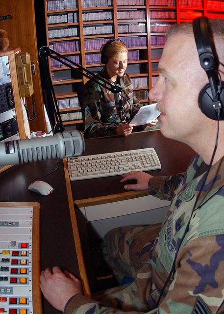 US Air Force (USAF) STAFF Sergeant (SSGT) April Lawrence (background), News Department, Non-Commissioned Officer In Charge (NOCIC), and US Air Force (USAF) Technical Sergeant (TSGT) Mike Burnette, NOCIC, Armed Forces Network (AFN) Radio, both assigned at Kaiserslautern, Germany, conduct a live broadcast for Kaiserslautern Military Community (KMC) members on the new Z 100.2 radio program. The AFN Kaiserslautern branch made new programming changes to better serve the KMC, by going to a 12-hour a day live, local broadcasting schedule