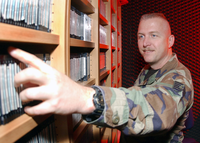 US Air Force (USAF) Technical Sergeant (TSGT) Mike Burnette, Non-Commissioned Officer In Charge (NOCIC), Armed Forces Network (AFN) Radio, Kaiserslautern, Germany, selects pre-recorded music to be broadcast for Kaiserslautern Military Community (KMC) members on the new Z 100.2 radio program. The AFN Kaiserslautern branch made new programming changes to better serve the KMC, by going to a 12-hour a day live, local broadcasting schedule