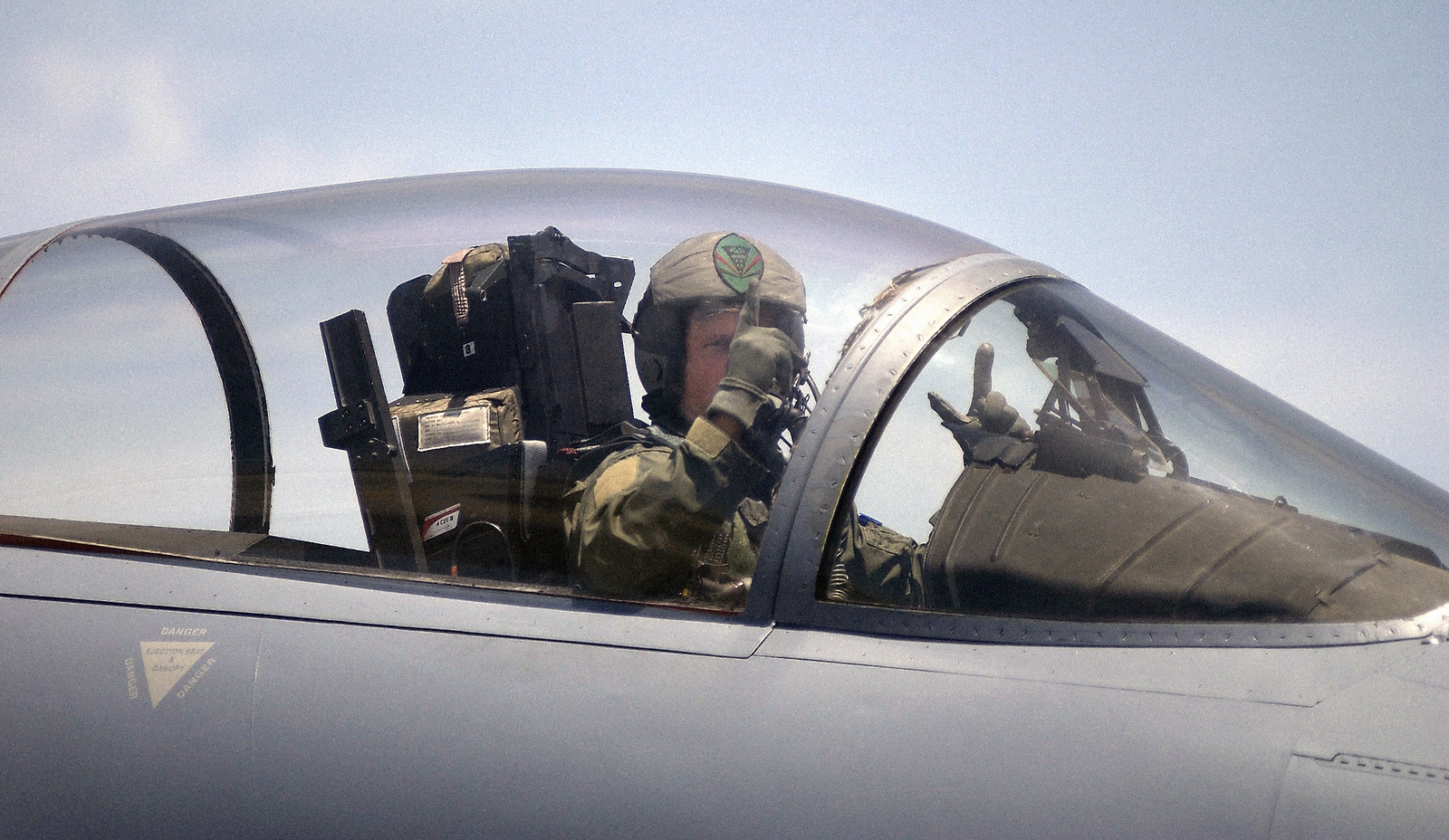 An unidentified US Air Force (USAF) F-15 Eagle aircraft pilot assigned to the 131st Fighter Wing (FW), Missouri (MO) Air National Guard (ANG), signals from the cockpit of his aircraft before takeoff for the Combat Search and Rescue (CSAR) training exercise DESERT RESCUE X, at Lambert International Airport (IAP), St. Louis, MO