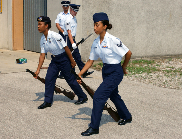"""US Air Force (USAF) AIRMAN First Class (AIC) Candace Sharp (left) and USAF SENIOR AIRMAN (SRA) On Theus, perform the """"ground arms"""" maneuver with their M-1 rifles during inspection drills for Wings Honor Guard, at Aviano Air Base (AB), Italy. This Drill Certification is an evaluation to see if they are ready to be promoted out of the training flight of the base Honor Guard"""