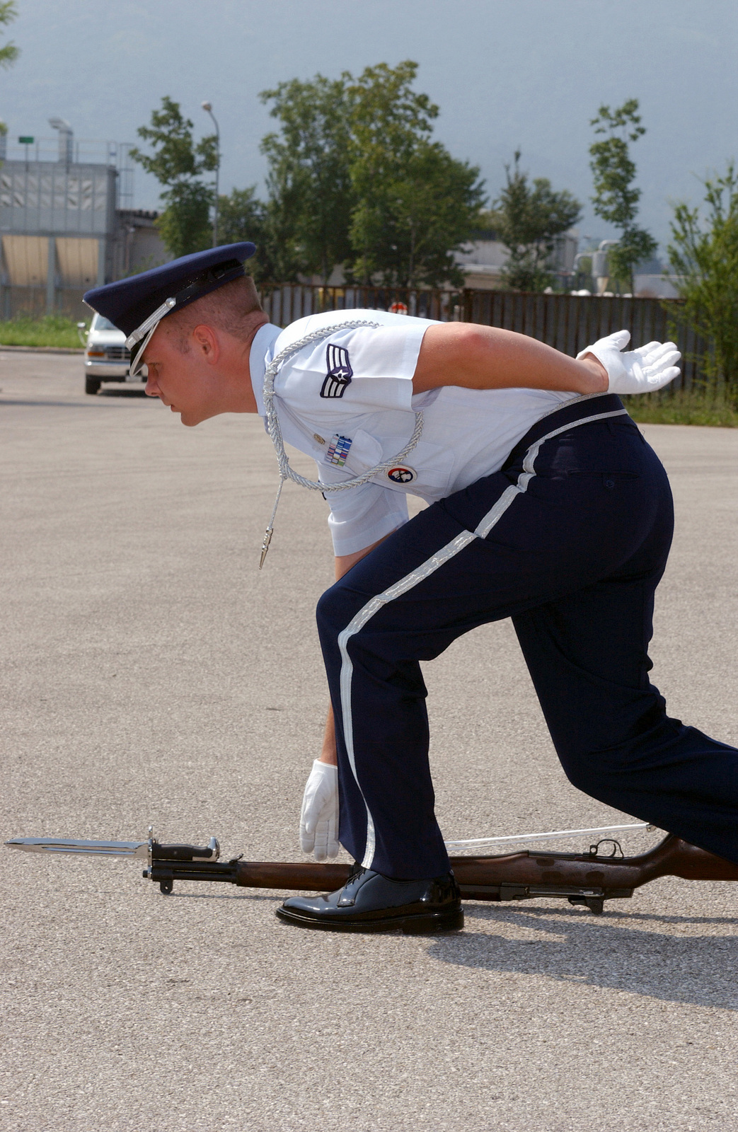 """US Air Force (USAF) SENIOR AIRMAN (SRA) Joshua Hodgin, a member of the 31st Fighter Wing (FW), Honor Guard performs the """"ground arms"""" maneuver with his M-1 rifle during inspection drills for Wings Honor Guard, at Aviano Air Base (AB), Italy"""