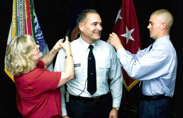 Brigadier General (BGEN) John M. Urias, (center), USA, promoted to Major General (MGEN). Placing the rank on him is his wife Heida and his son John, stationed at Fort Gordon, Georgia. BGEN Urias serves as both the Commander of Research, Development and Acquisition (DCG-RDA), U.S. Army Space and Missile Defense Command (SMDC) and the Program Executive Officer for Air and Missile Defense (PEO AMD)