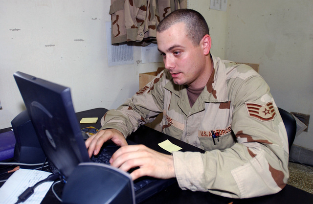 US Air Force (USAF) STAFF Sergeant (SSGT) Jason Thoel, Non-commissioned Officer in Charge (NCOIC), Communications Focal Point, 438th Expeditionary Supply Squadron (ESS), 438th Air Expeditionary Wing (AEW), uses a laptop computer to establish new user account for newly assigned personnel at a forward deployed location in support of Operation ENDURING FREEDOM