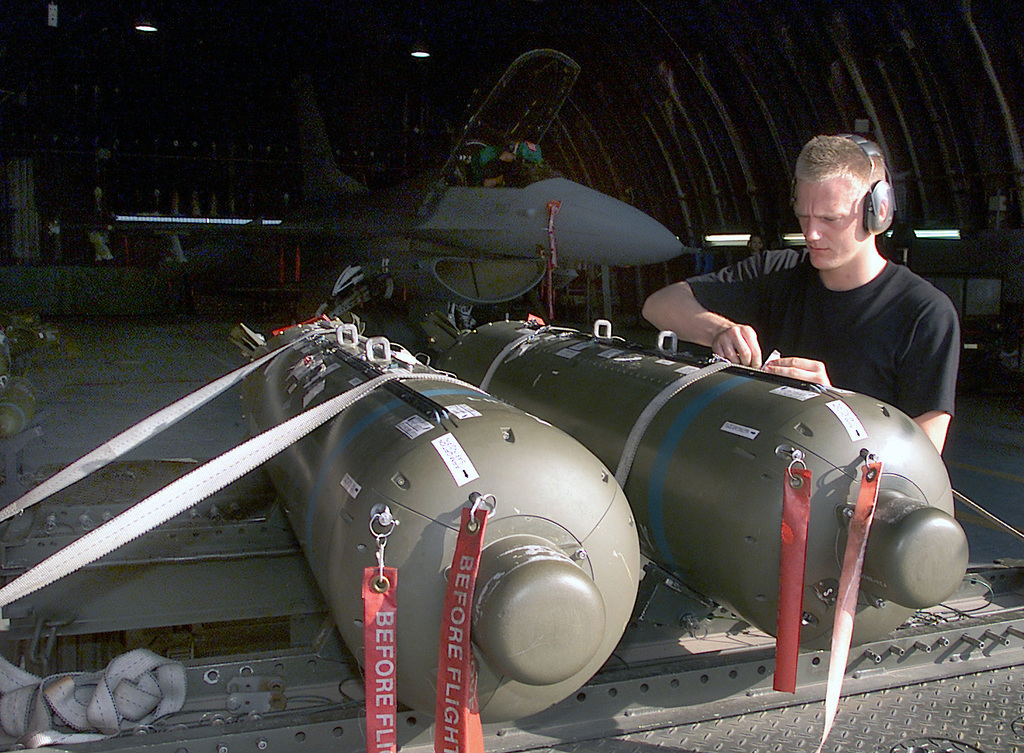 US Air Force (USAF AIRMAN First Class (A1C) Jason Warner, Weapons Standardization Evaluator, inspects CBU-87 cluster bombs, secured atop a munitions trailer, before the are loaded onto a USAF F-16C Fighting Falcon aircraft at Aviano Air Base (AB), Italy