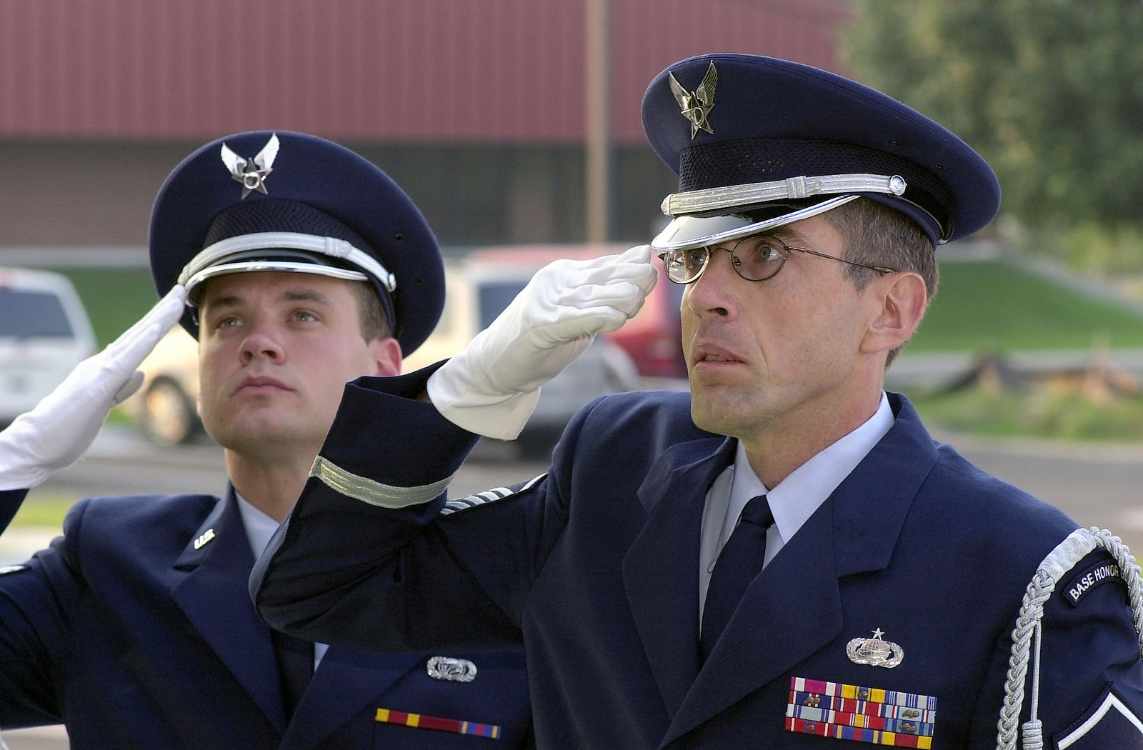 US Air Force (USAF) SENIOR AIRMAN (SRA) Mickey Uphold (left) and USAF MASTER Sergeant (MSGT) Paul Hammond, both assigned to 138th Fighter Wing (FW), Oklahoma (OK), Air National Guard (ANG) Honor Guard, stand and salute as the flag is raised in front of the new Headquarters and Support Complex Building for the 138th FW, Tulsa, International Airport (IAP), located in Tulsa, OK