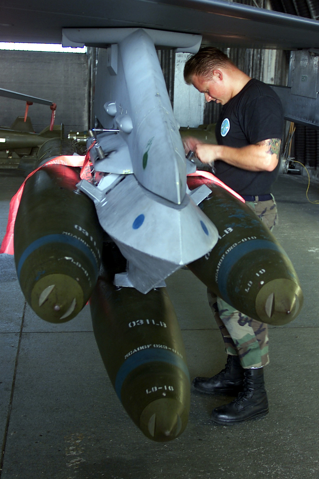 US Air Force (USAF) STAFF Sergeant (SSGT) Vincent Horn, Weapons Standardization Evaluator, secures MK-82 500-pound general-purpose bombs to a triple ejector rack attached to the wing pylon of a USAF F-16 Fighting Falcon aircraft at Aviano Air Base (AB), Italy