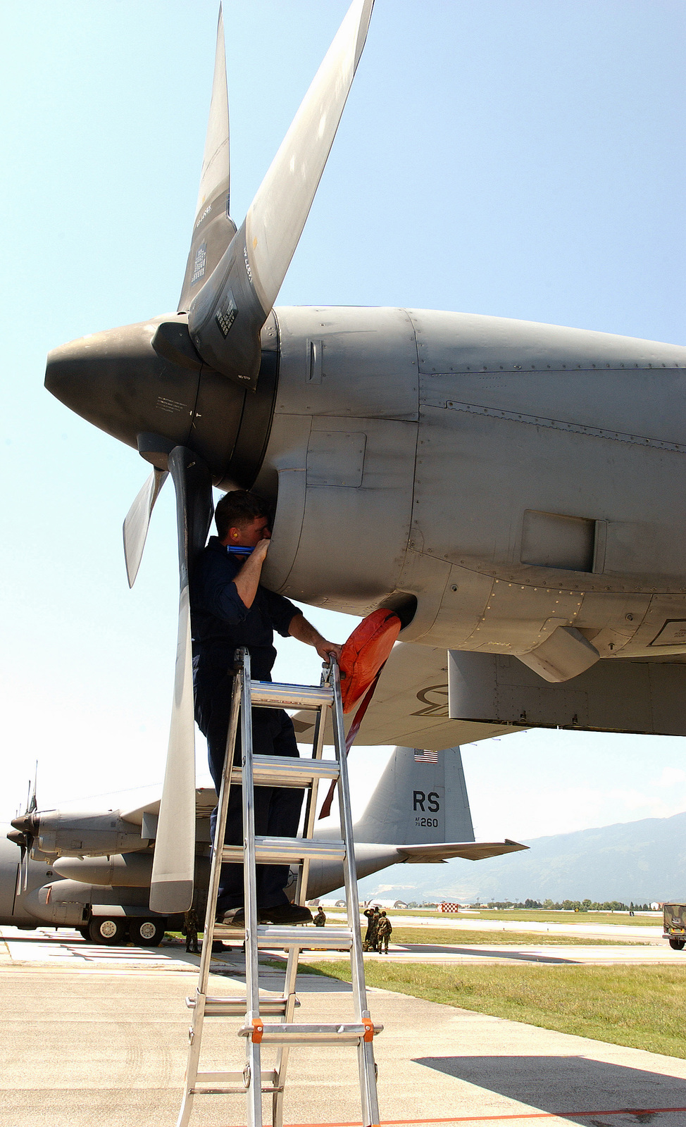 US Air Force (USAF) Technical Sergeant (TSGT) George Nunn, 37th Airlift Wing (AW) uses a ladder to perform an intake and exhaust inspection on a USAF C-130 Hercules aircraft on the flight line at Aviano Air Base (AB), Italy