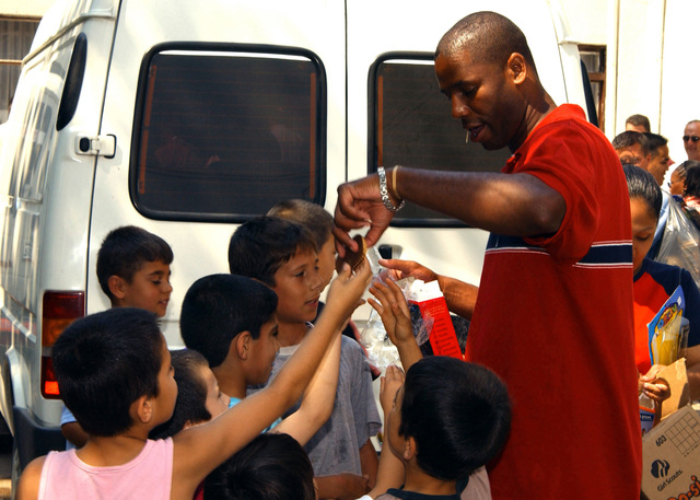 US Air Force (USAF) STAFF Sergeant (SSGT) Gerald Redd (center) distributes cookies to Turkish children at an orphanage in Mersin, Turkey. SSGT Redd is deployed to Incirlik Air Base (AFB), Turkey, from the 48th Fighter Wing (FW), Royal Air Force (RAF) Lakenheath, United Kingdom, (UK) in support of Operation NORTHERN WATCH