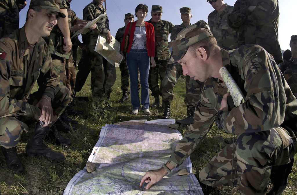 US Army (USA) Captain (CPT) Kelly Smith (foreground left), 10th Special Forces Group (Airborne), uses a map to explain terrain changes for a war-gaming scenario, before conducting a staff ride with Georgian Army Officers attending the Georgia Train and Equip Program (GTEP) at Tbilisis, Georgia. GTEP conducted by the US Army European Command, is designed to enhance the capability of selected Georgian military units to provide security and stability to the citizens of Georgia and the region