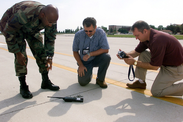 A panel of experts examines a portion of the runway at Aviano Air Base (AB), Italy, discovered to be damage by lighting from the previous night's storm. Pictured left-to-right US Air Force (USAF) MASTER Sergeant (MSGT) Courtney Davis, Air Field Manger, 31st Operations Support Squadron; Mr. Aleksander Andrzejewski, Detachment 3, 16th Air Force Program Management Office; and Dr. Randall Brown, Headquarters Air Force Civil Engineering Support Agency