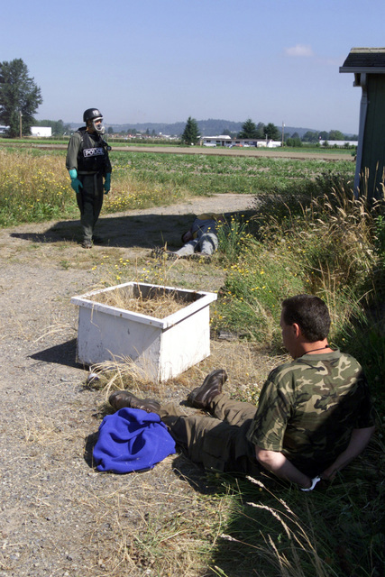 An Officer with the Pierce County, Washington (WA) Police Department, stands guard over two suspected terrorists during a simulated chemical weapons exercise conducted at McChord Air Force Base (AFB), Fort Lewis, WA, during Exercise SEAHAWK 2002. Seahawk combines active duty and reserve components from the US Air Force (USAF), US Navy (USN), US Coast Guard (USCG), US Public Health Service, Royal Canadian Armed Forces (RCAF), Federal Bureau of Investigation (FBI), Federal Emergence Management Association (FEMA) and multiple civilian first responder agencies in coordinated responses to simulated terrorist acts inside the Continental United States (CONUS) and outside (OCONUS) environments....