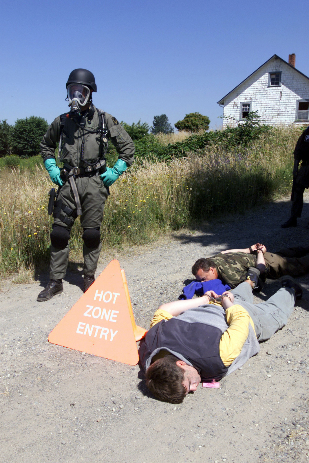 An Officer with the Pierce County, Washington (WA) Police Department, wearing Nuclear, Biological, Chemical (NBC) gear stands guard over two suspected terrorists during a simulated chemical weapons exercise conducted at McChord Air Force Base (AFB), Fort Lewis, WA, during Exercise SEAHAWK 2002. Seahawk combines active duty and reserve components from the US Air Force (USAF), US Navy (USN), US Coast Guard (USCG), US Public Health Service, Royal Canadian Armed Forces (RCAF), Federal Bureau of Investigation (FBI), Federal Emergence Management Association (FEMA) and multiple civilian first responder agencies in coordinated responses to simulated terrorist acts inside the Continental United...