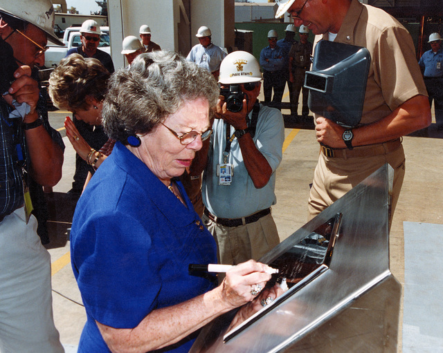 Mrs. Elaine Williams, Widow of the ship's namesake, US Navy (USN) PETTY Officer First Class (PO1) James E. Williams, is shown signing her initials onto the authentication plate at the official keel laying for the US Navy (USN) ARLEIGH BURKE CLASS (FLIGHT IIA) GUIDED MISSILE DESTROYER (AEGIS) USS JAMES E. WILLIAMS (DDG 95)