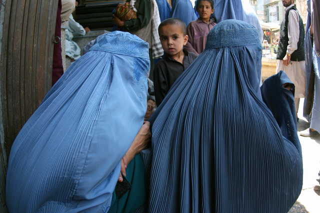 Two local Afghan women dressed in birkas, sit on the sidewalk of the market in downtown Kabul, Afghanistan, while waiting for their families to finish shopping