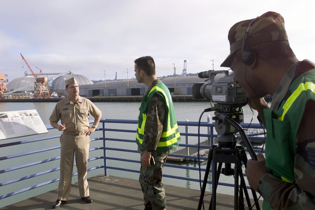 US Navy (USN) Rear Admiral (RADM) Marke R. Shelley (left), Commander, Maritime Defense Zone Pacific, is videotaped during an interview with US Air Force (USAF) First Lieutenant (1LT) Hamilton Underwood (center) and USAF STAFF Sergeant (SSGT) Jerome Turner, both assigned to the 4th Combat Camera Squadron (CCS), prior to the start of Exercise SEAHAWK 2002. Seahawk combines active duty and reserve components from the US Air Force (USAF), US Navy (USN), US Coast Guard (USCG), US Public Health Service, Royal Canadian Armed Forces (RCAF), Federal Bureau of Investigation (FBI), Federal Emergence Management Association (FEMA) and multiple civilian first responder agencies in coordinated...