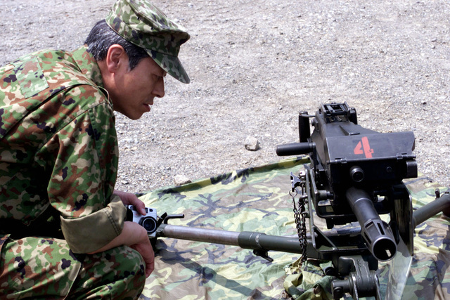 A cameraman, from a Japanese television station, looks over an MK19 40mm Machine Gun, MOD 3 at a display of small arms firing weapons during Media Day at the Ojojihara Maneuvering Area before the OJOJIHARA ARTILLERY LIVE FIRE Exercise kick off in Ojojihara, Japan