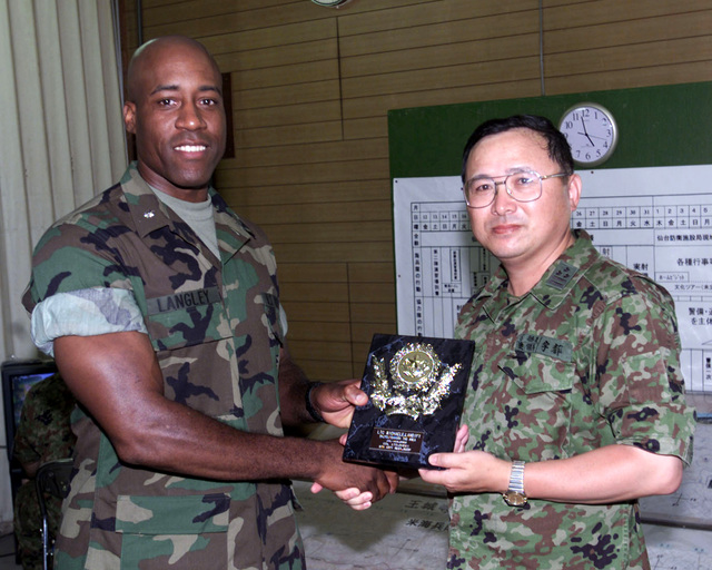 Marine Lieutenant Colonel (LCOL) Richaele Langley, USMC, accepts a plaque from a Japanese Officer at the Ojojihara Maneuvering Area during the OJOJIHARA ARTILLERY LIVE FIRE