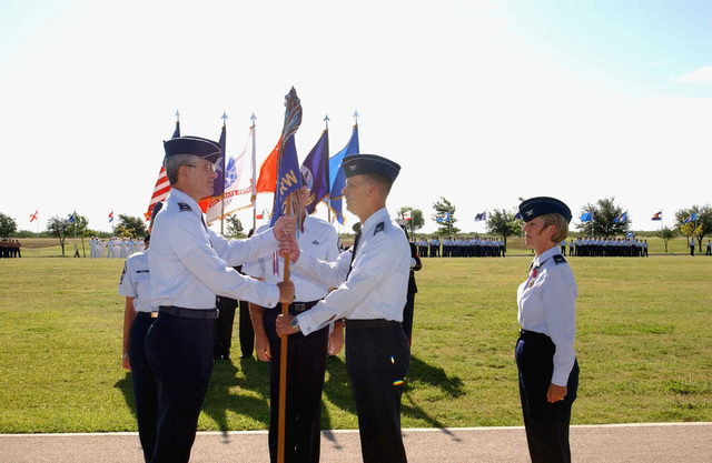 US Air Force (USAF) Major General (MGEN) John Regni (left), Commander, Second Air Force, passes the Unit Flag to USAF Colonel (COL) Martin Neubauer, during the 17th Training Wing (TRW) Change of Command Ceremony, held at Goodfellow Air Force Base (AFB), Texas (TX). USAF COL K.C. McClain, Out-going Commander looks on