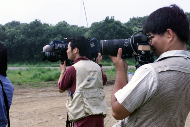 Japanese cameramen from local Japanese newspapers taking pictures of Marines on Media Day at the Ojojihara Manuevering Area during the OJOJIHARA ARTILLERY LIVE FIRE Exercise in Ojojihara, Japan