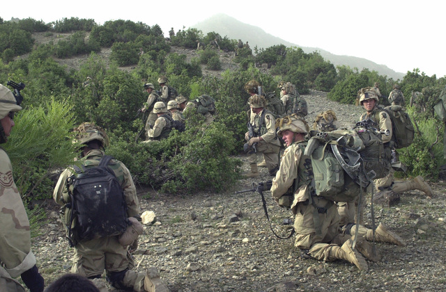 US Army (USA) Soldiers assigned to Alpha Company, 3rd Battalion, 187th Infantry Regiment, 101st Airborne Division, pause to take a brake as the conduct search and attack mission, in the mountains located near Narizah, Afghanistan, during Operation ENDURING FREEDOM