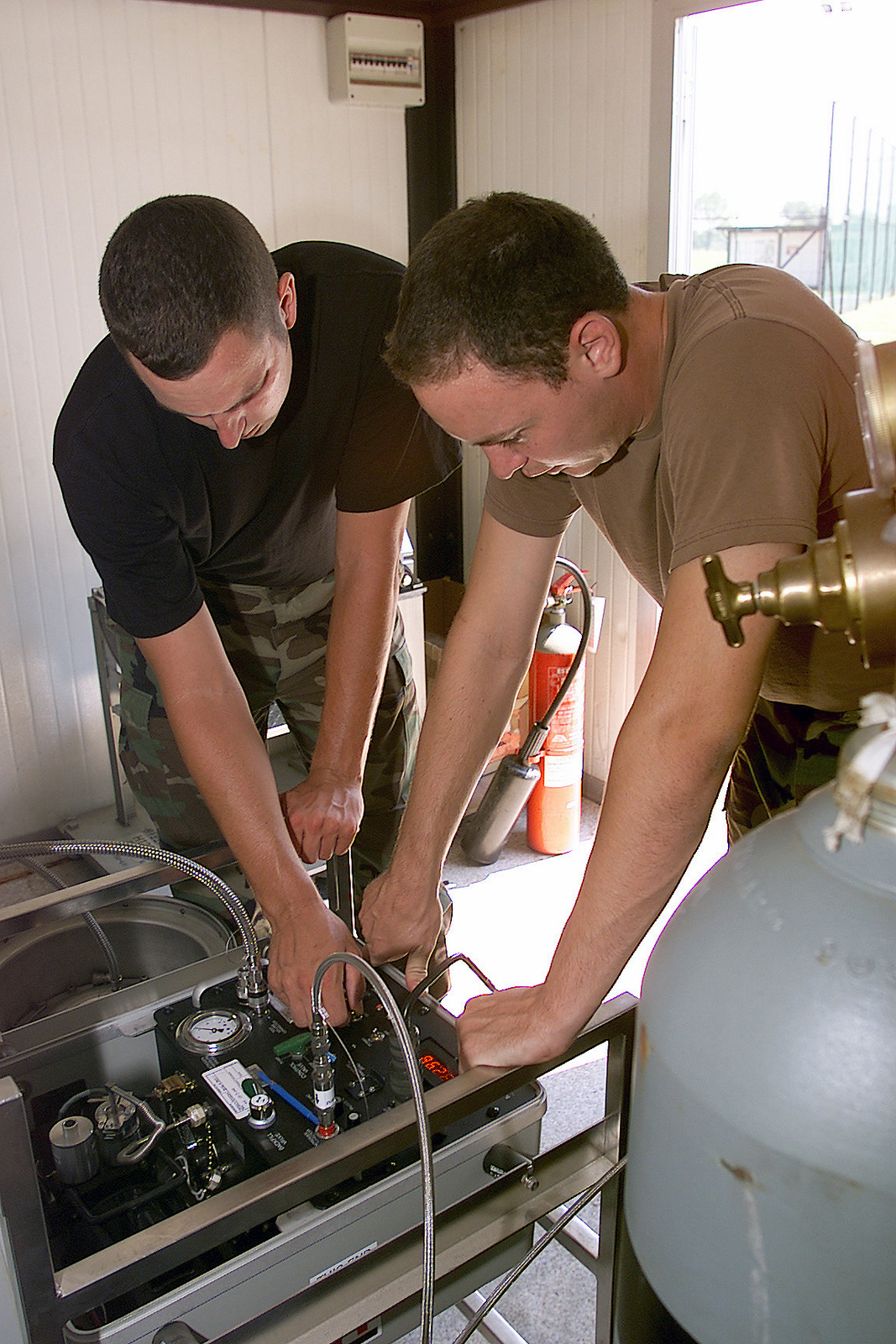 US Air Force (USAF) STAFF Sergeant (SSGT) Craig Ratliff (left) and USAF SSGT Morgan Ard, both Weapons Specialists assigned to the 831st Munitions Support Squadron (MSS), operate a vacuum pump during a weapons shipment, at Ghedi Air Base (AB), Italy