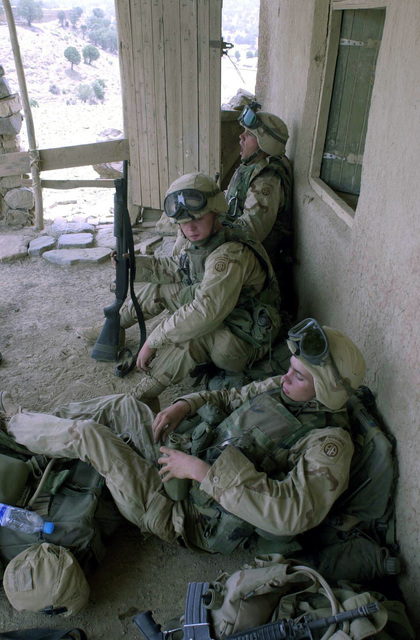 US Army (USA) Soldiers assigned to1-505th Parachute Infantry Regiment, rest next to a structure, as they man a security perimeter during a medical assistance mission in the town of Keyki, Afghanistan, during Operation ENDURING FREEDOM. The medical assistance mission was conducted as a reward for the local residents, for not interfering with forces that are conducting a sensitive site exploration in the caves surrounding the town