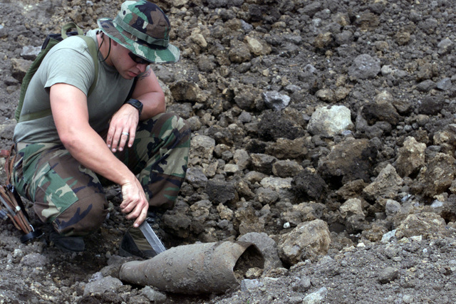 A Marine checks out a spent M107 155mm High Explosive Round on the Ojojihara Maneuvering Area range. The Marines collected the rounds, along with other munitions left by other units that trained in Ojojihara, to dispose of them