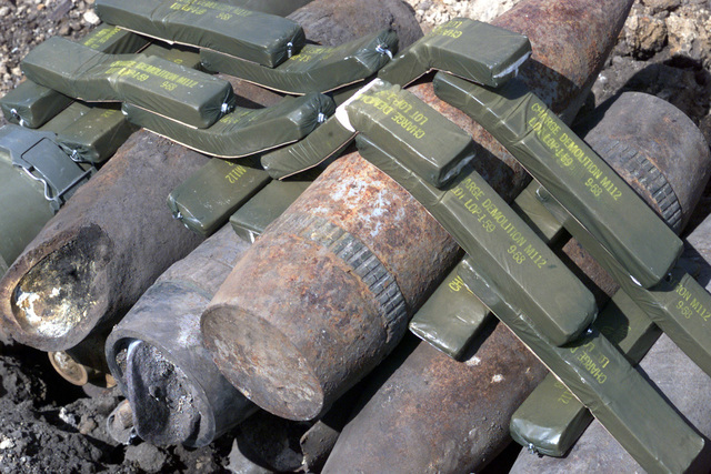 A stack of M107 High Explosive Rounds that did not work properly during exercises at the OJOJIHARA ARTILLERY LIVE FIRE Exercise. The Marines collected the rounds, along with other munitions left by other units that trained in Ojojihara, and disposed of them using several blocks of M112 Composition C4 Demolition Charge