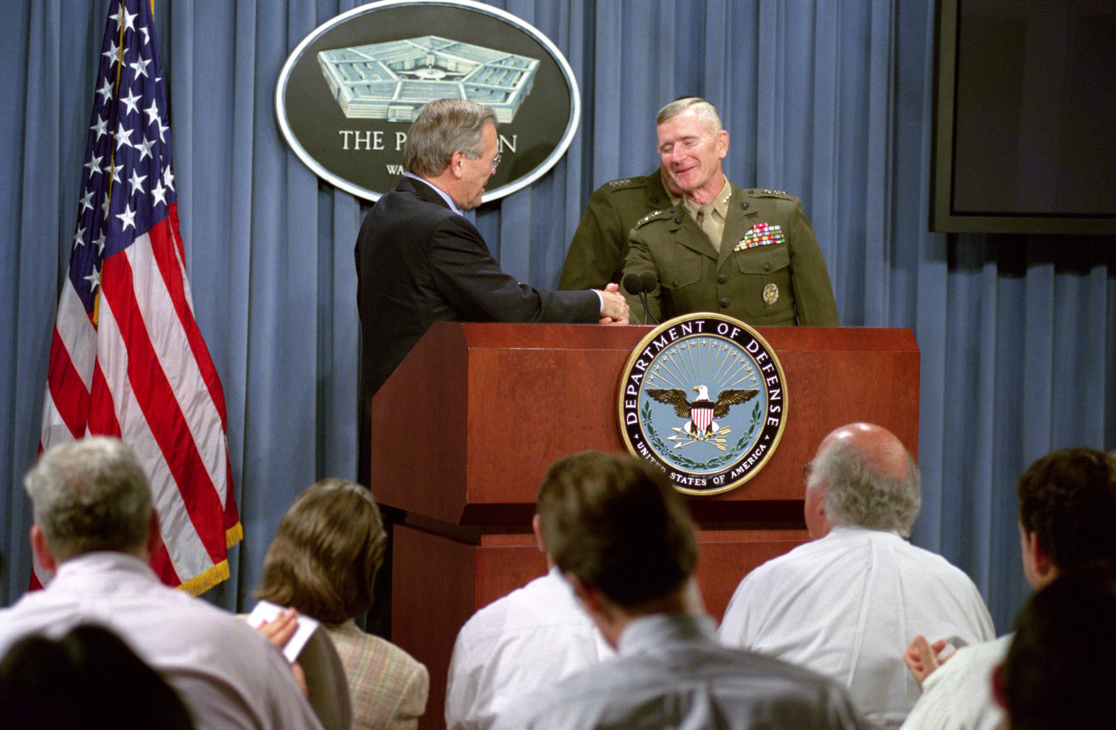 The Honorable Donald H. Rumsfeld (left), U.S. Secretary of Defense (SECDEF), and U.S. Marine Corps GEN. Peter Pace (rear, obscured), Vice Chairman of the Joint Chiefs of STAFF, conduct an operational update briefing at the Pentagon, Washington, D.C., on July 30, 2002.  The SECDEF shakes the hand of GEN. Gregory Newbold, frequent news briefer, after announcing his retirement from Active Service.  OSD Package No. A07D-00588 (DOD PHOTO by Robert D. Ward) (Released)
