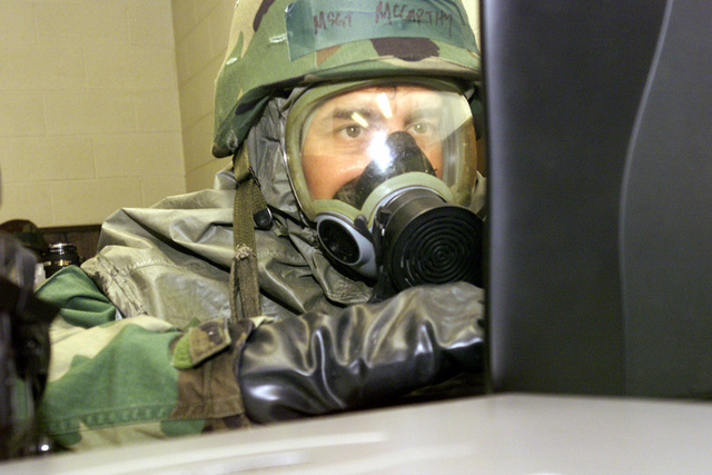 US Air Force (USAF) MASTER Sergeant (MSGT) David McCarthy, 4th Combat Camera Squadron (CCS), wears his Mission-Oriented Protective Posture response level 4 (MOPP-4) gears as he inputs images into his laptop computer during a simulated chemical attack, conducted during Exercise CRISIS REACH 02-19B, at the Combat Readiness Training Center (CRTC), located at the Savannah International Airport (IAP), Georgia (GA)