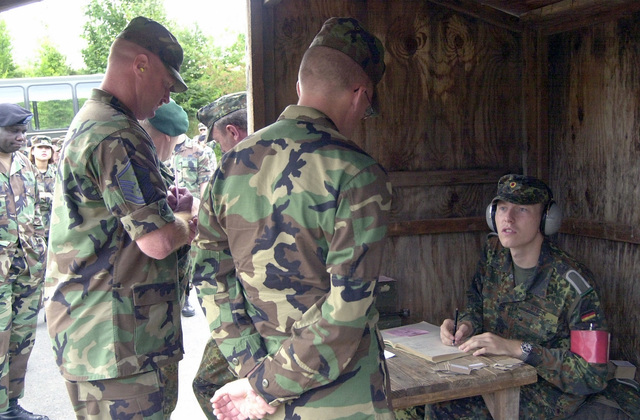 During a competition for the German shooting medal, the Shutzensnur, US Air Force (USAF) MASTER Sergeant (MSGT) Russell Harrington, First Sergeant (1SGT) of the 886th Communication Squadron (CS), Sembach Annex, Germany, turns in his score card prior to firing a German MG42 7.92mm machine gun, the equivalent of our M-60 7.62mm machine gun