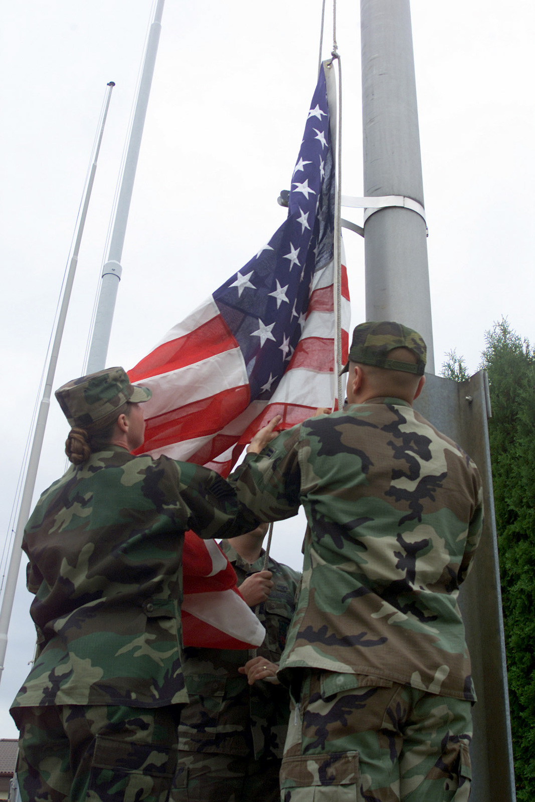 US Air Force (USAF) Honor guard members with the 52nd Fighter Wing (FW), lower the American Flag during Spangdahlem's Remembrance Ceremony on Patriots Day, at Spangdahlem Air Base (AB), Germany