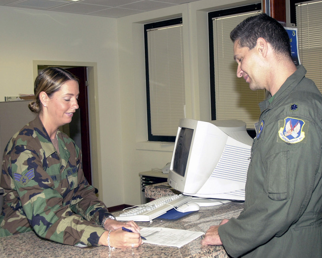 US Air Force Reserve (USAFR) SENIOR AIRMAN (SRA) Michelle Morrow (left), 910th Communications Flight, assists a customer inside the Military Personnel Flight (MPF) while deployed with the 31st Communication Squadron (CS), at Aviano Air Base (AB), Italy, for her two-week annual tour
