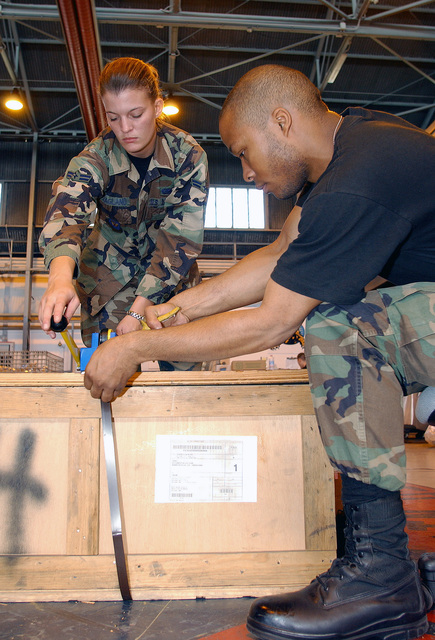 US Air Force (USAF) AIRMAN First Class (A1C) Cari Ragland (left) and USAF A1C Leotis Ott, both assigned to the 31st Supply Squadron, strap a wooden crate with metal bands as they prepare the crate for shipment at Aviano Air Base (AB), Italy