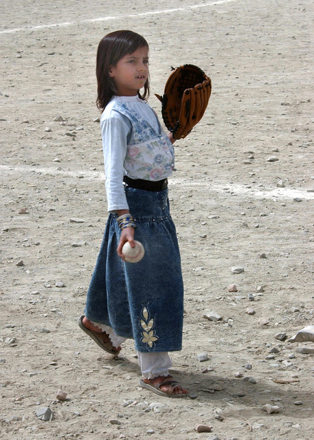An Afghani girl plays with her baseball and glove at Camp Harriman, located in the Orgun Province of Afghanistan, during Operation ENDURIG FREEDOM. Mr. Jay Smith, 96th Civil Affairs Battalion, donated the baseball equipment and this girl is reportedly the first Afghani girl, from her area, to ever own a ball and glove