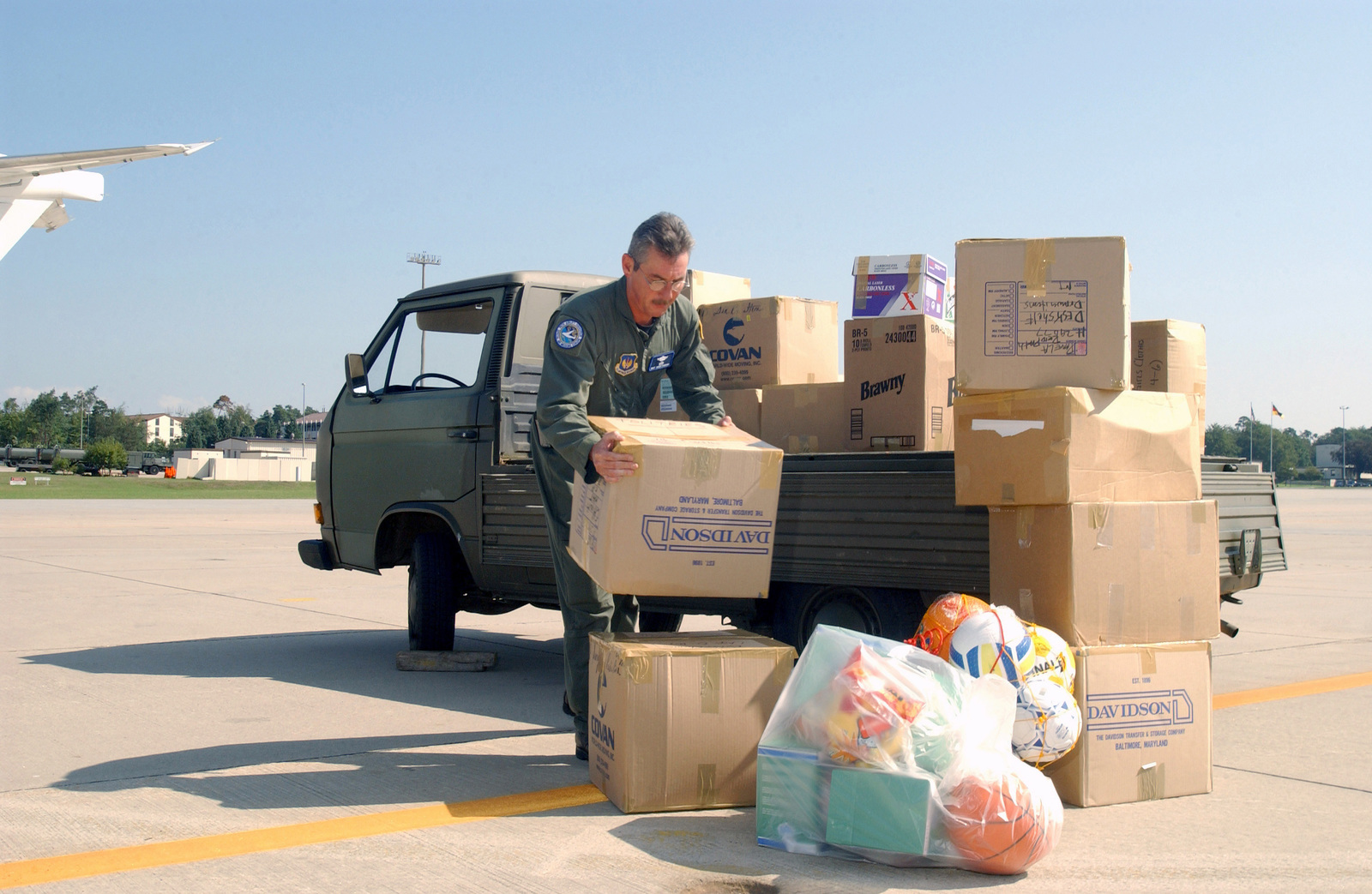 US Air Force (USAF) MASTER Sergeant (MSGT) Johnny MacMahan, a Radio Operator from the 76th Airlift Squadron (AS), 86th Airlift Wing (AW), Ramstein Air Base (AB), Germany, loads boxes of school supplies, food and clothing donated by Kaiserslautern Military Families, destined for the country of Moldova