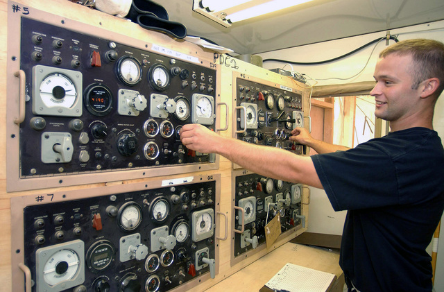 US Air Force (USAF) AIRMAN First Class (A1C) Michael Chuning, Electrical Power Production Journeyman, 438th Expeditionary Civil Engineering Flight (ECEF), balances the frequency between two 750-kilowatt Mobile Electric Power (MEP-12) generators while deployed at a forward location supporting Operation ENDURING FREEDOM