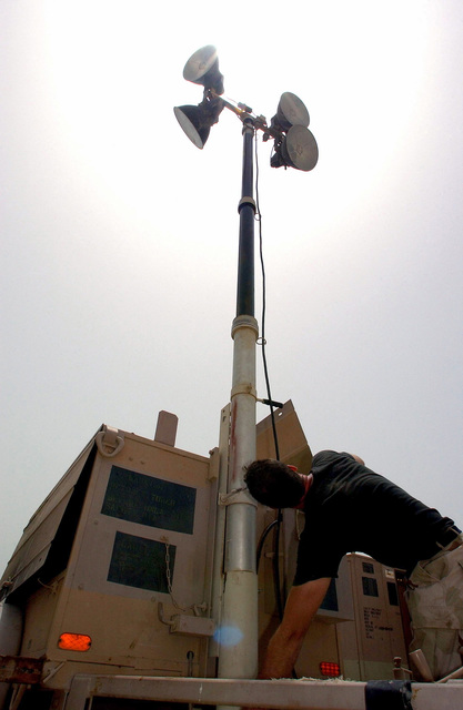 US Air Force (USAF) SENIOR AIRMAN (SRA) Jeremy Tripp, an Electrical Power Production Journeyman, 438th Expeditionary Civil Engineering Flight (ECEF), raises the boom on a telescopic flood light, outside the new laundering facility while deployed at a forward location supporting Operation ENDURING FREEDOM