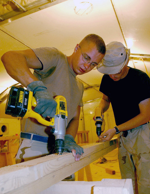 US Air Force (USAF) AIRMAN First Class (A1C) Benjamin Jensen (foreground), Structural Journeyman, and USAF STAFF Sergeant (SSGT) Richard Panepinto, Structural Craftsman, both assigned to the 438th Expeditionary Civil Engineering Flight (ECEF), work to construct rafters for a new patio addition to the Base Chapel, while deployed at a forward location supporting Operation ENDURING FREEDOM