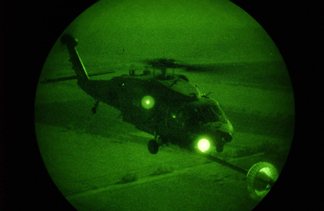 Light enhanced photography, fisheye lens view, showing a US Air Force (USAF) UH-60 Black Hawk helicopter assigned to the 41st Expeditionary Rescue Squadron (ERQS), in flight refueling from a USAF HC-130P Hercules aircraft, during an exercise flow in support of Operation ENDURING FREEDOM