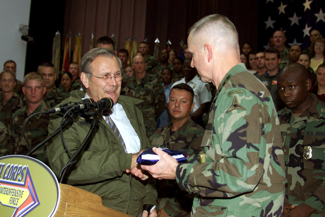 The Honorable Donald H. Rumsfeld (left), U.S. Secretary of Defense, presents a U.S. Flag that flew over the Pentagon to U.S. Army LT. Gen. Burwell B. Bell (right), Commander, III Corps and Fort Hood, at the end of the Secretary's Town Hall Meeting in Howze Theater, Fort Hood, Texas, on Aug. 21, 2002. (U.S. Army photo by Christopher J. Varville) (Released)