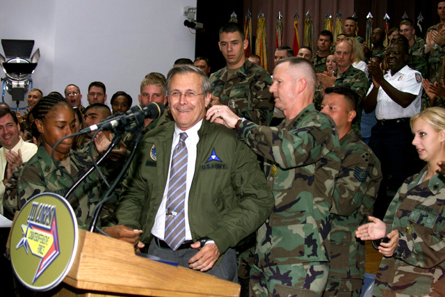 The Honorable Donald H. Rumsfeld (second from left), U.S. Secretary of Defense, is presented with an Armored Crewman Tanker's jacket by U.S. Army STAFF SGT. Canndice Taylor (left), III Corps Non-Commissioned Officer of the Year, and LT. Gen. Burwell B. Bell (second from right), Commander, III Corps and Fort Hood, during the Secretary's Town Hall Meeting in Howze Theater, Fort Hood, TX, on Aug. 21, 2002. (U.S. Army photo by Christopher J. Varville, CIV) (Released)