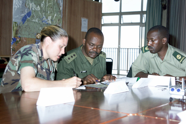 Multinational Soldier participating in Exercise MEDFLAG 02-1, sit down an map out a possible route from the city of Entebbe, Uganda, to a forward operating location during the Exercise. Pictured left-to-right US Army (USA) Captain (CPT) Michelle Snyder, Army Intelligence Officer; Republic of Uganda Army Captain (CPT) Karugaba Godwin Ugandan Logistics Officer; and Republic of Rwandan Army Major (MAJ) Rugazora Emanuel. MEDFLAG is a US European Command multinational multi-service medical exercise designed to provide care, training and disaster management for Doctors, Nurses, and Technicians in different countries around the world